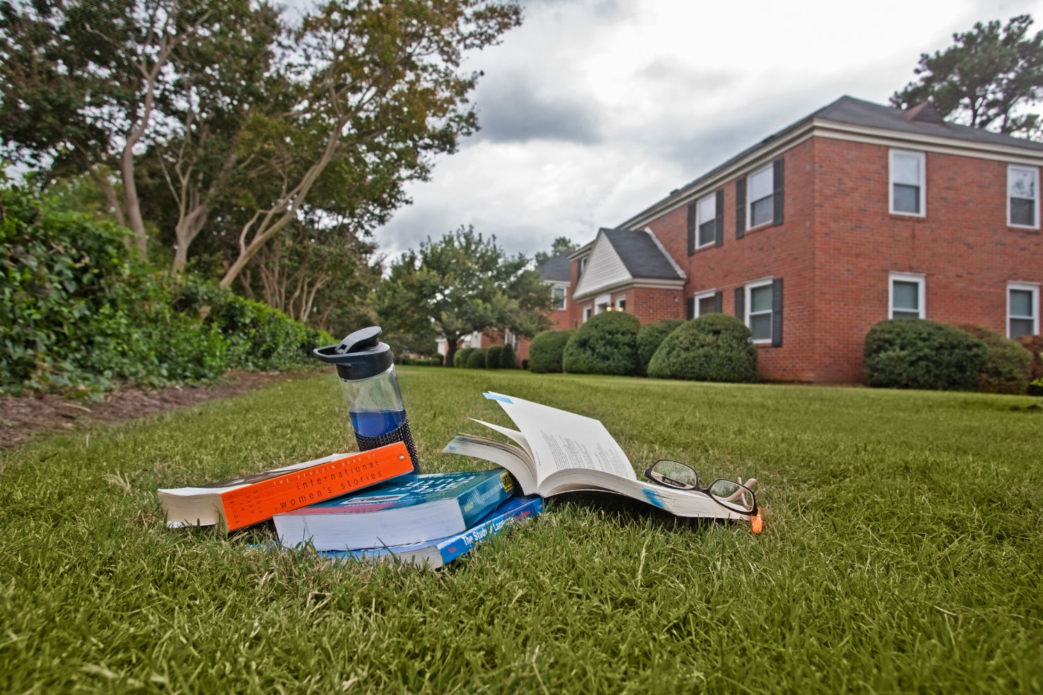 Exterior building and student books on lawn